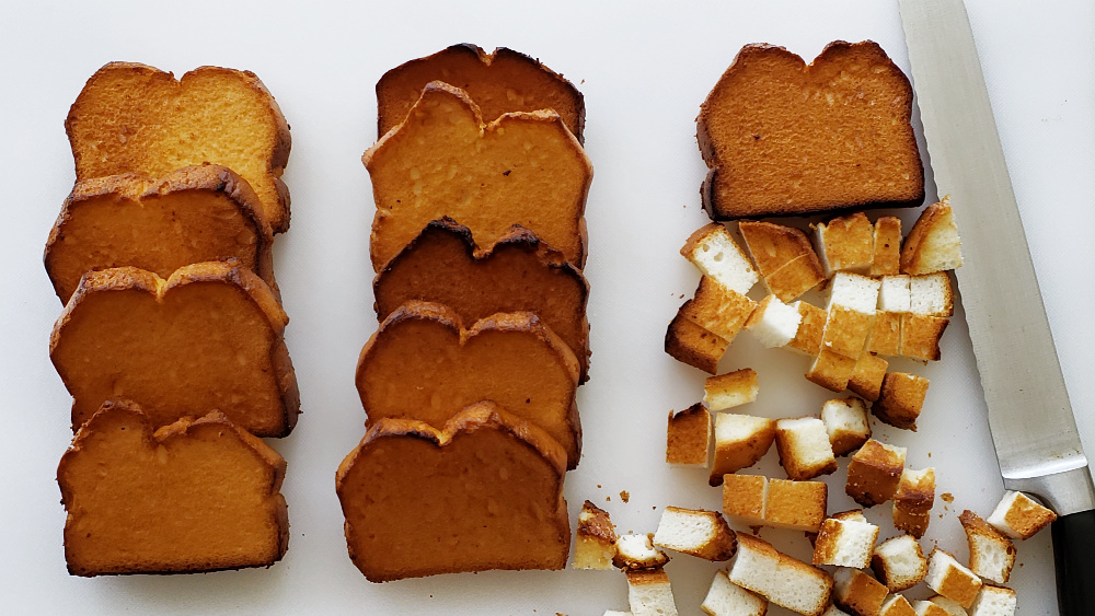10 pieces of toasted angel food cake lined up with 1 piece cut into cubes on a white board