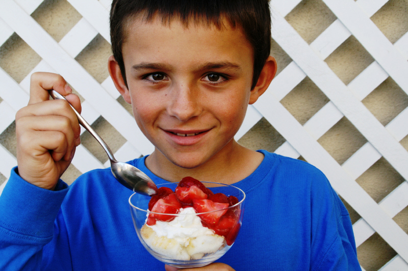 Young boy in a blue shirt eating Strawberry Cloud Dessert in a front of a white lattice fence