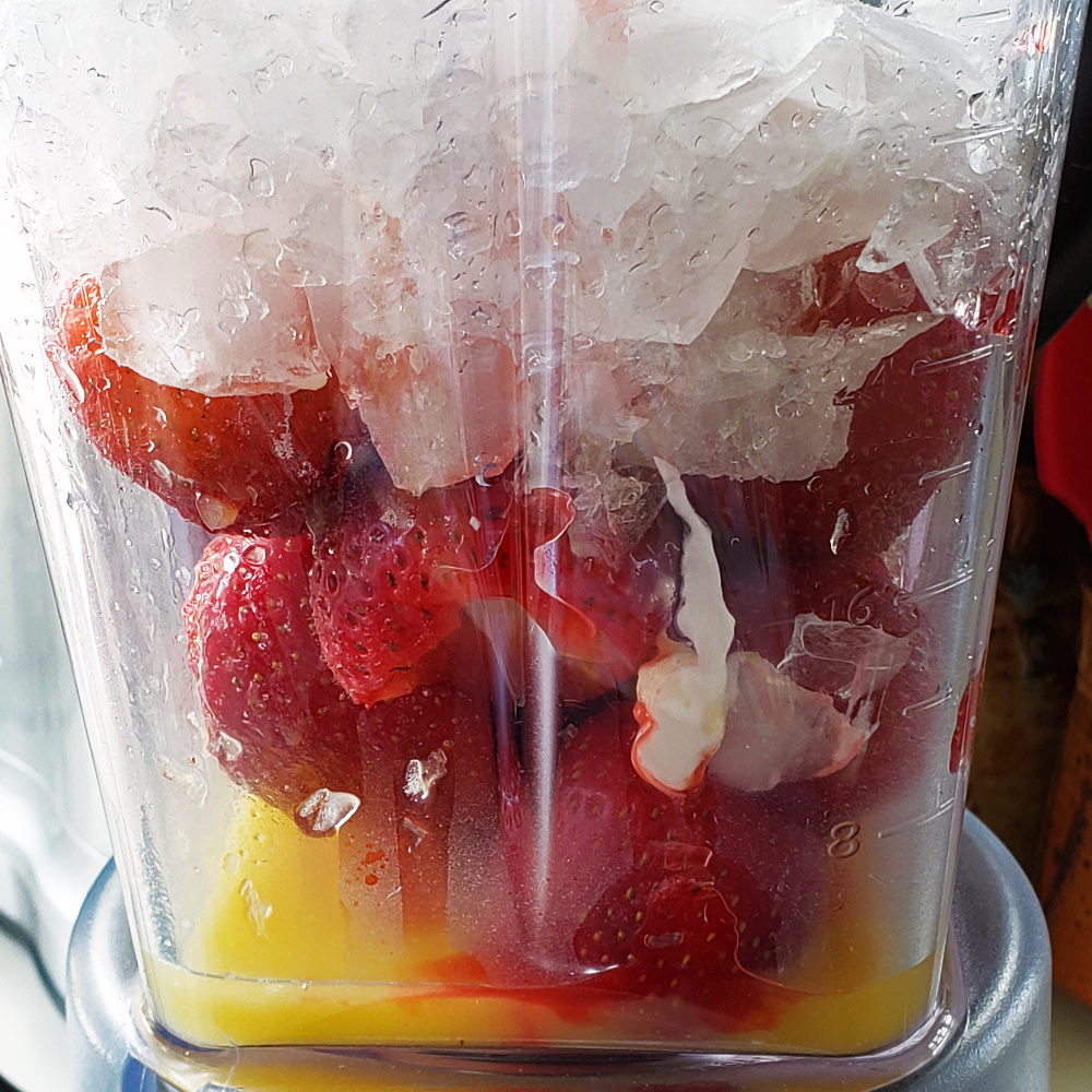 Orange juice, strawberries, yogurt and ice -- Ingredients for in blender on ShockinglyDelicious.com