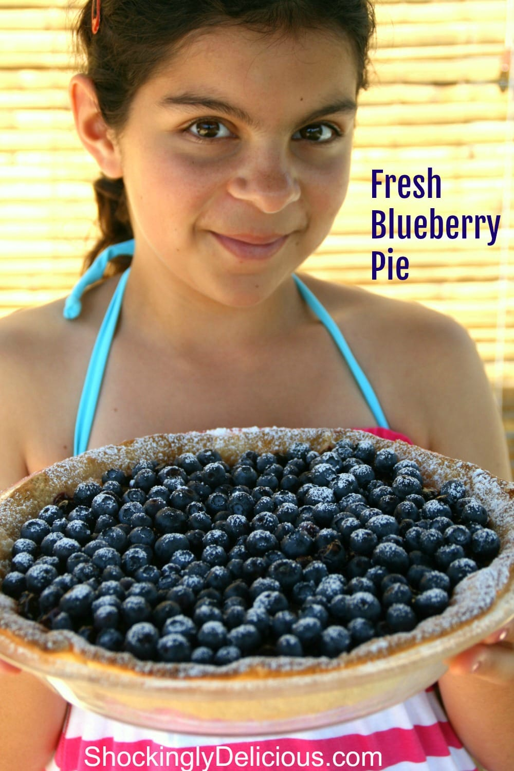 Young girl shows off a whole Fresh Blueberry Pie on ShockinglyDelicious.com