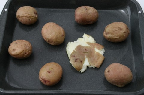 Red potatoes on a grey baking pan