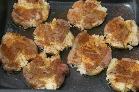 Smashed Potatoes with seasoning on top on a baking pan