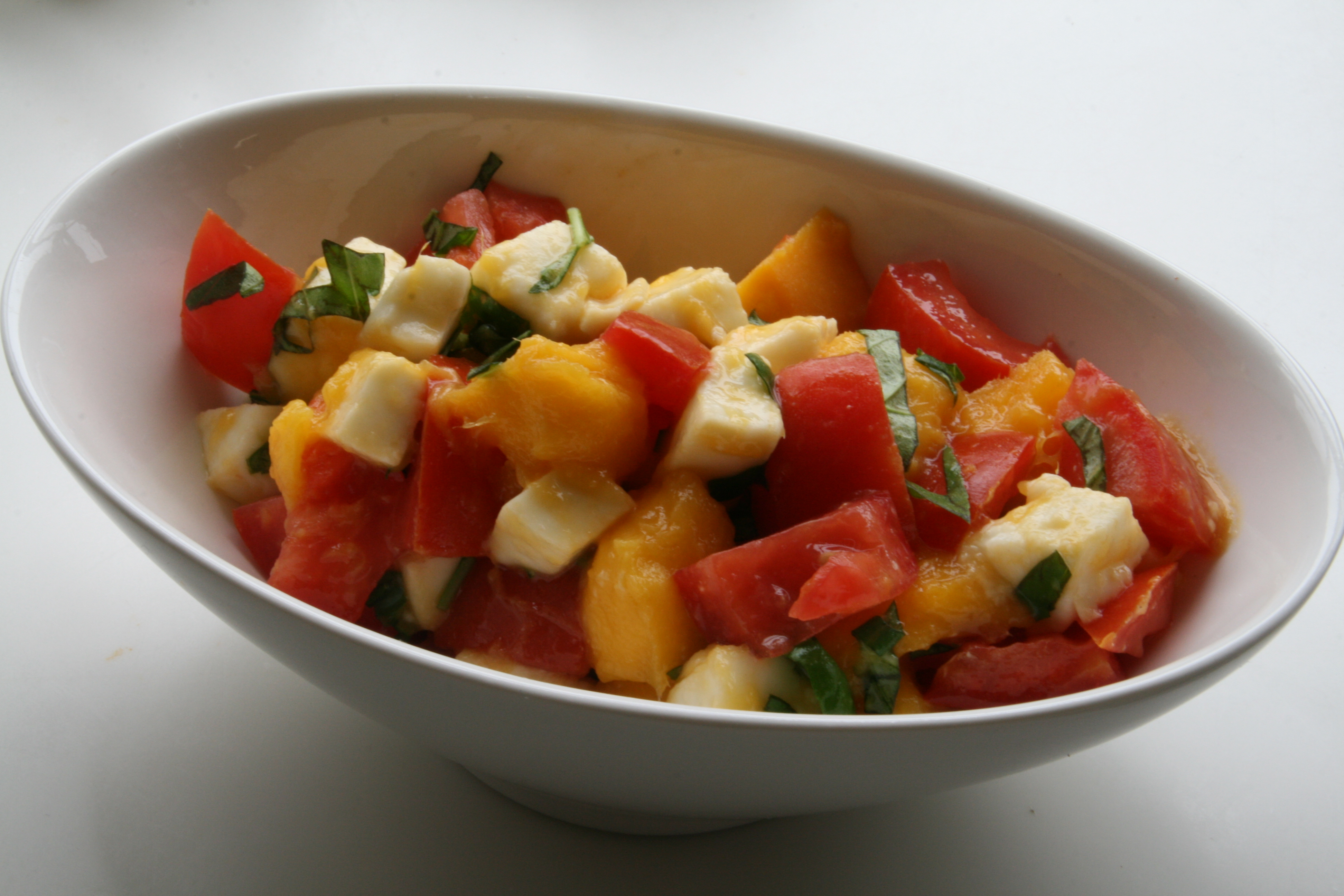 Mango Caprese Salad in a white oval bowl