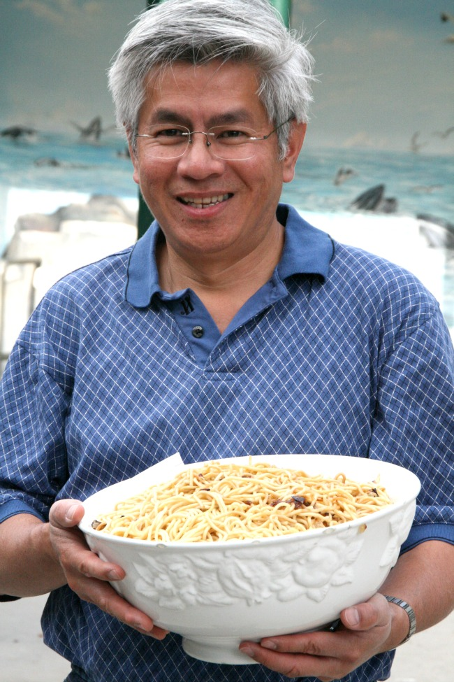 Hung Le holding a white bowl of his famous fried spaghetti