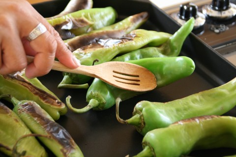 Wooden spoon tamps down Hatch chile on griddle