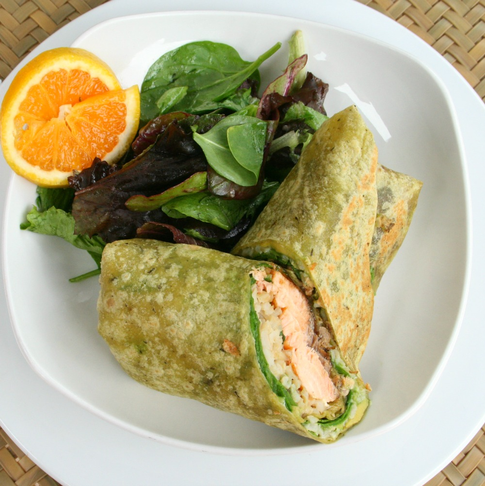 Salmon Wrap Sandwich on a white plate with a salad and orange slices alongside