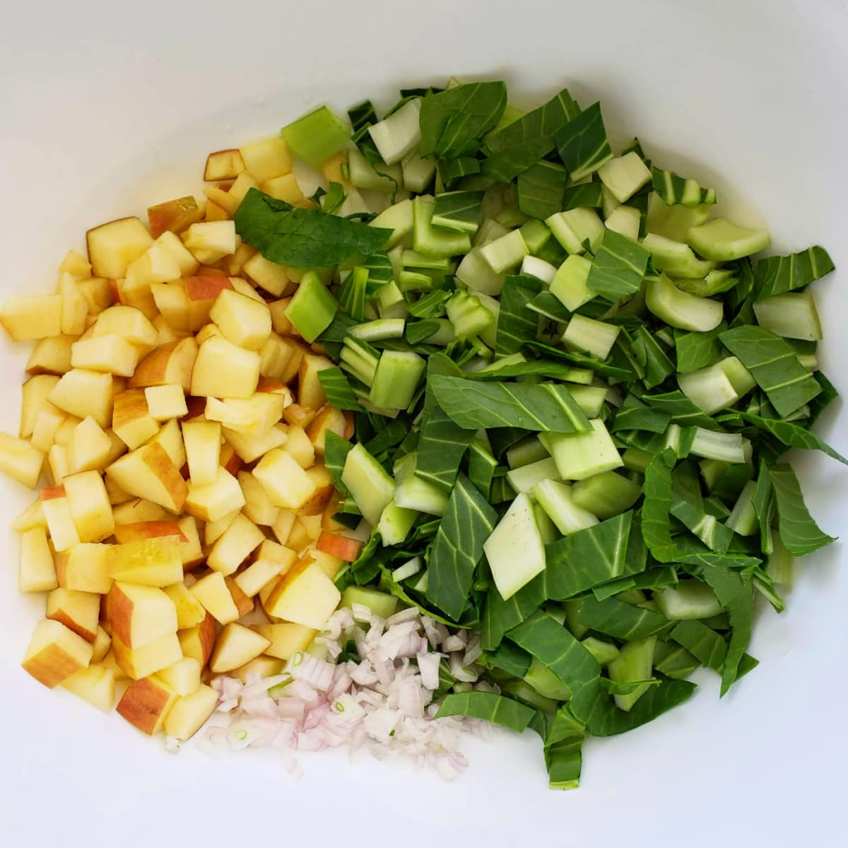 Aerial view of chopped baby bok choy, apple and shallot in a white mixing bowl