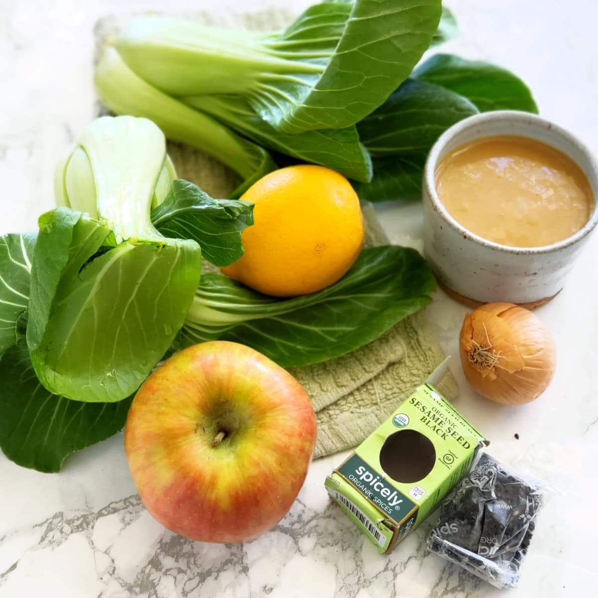 Ingredients for Lemony Baby Bok Choy Apple and Miso Salad -- bok choy, apple, lemon, shallot, black sesame seeds and dressing, on a marble countertop