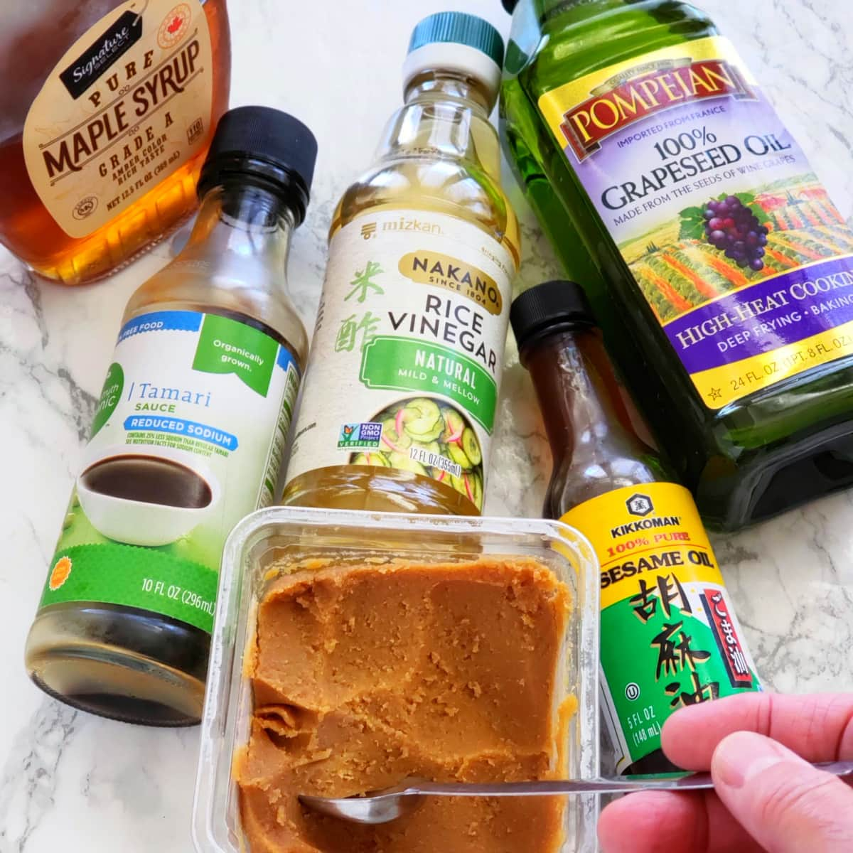 Ingredients for Sweet Miso Dressing -- maple syrup, tamari, rice vinegar, grapeseed oil, white miso and sesame oil on a marble countertop