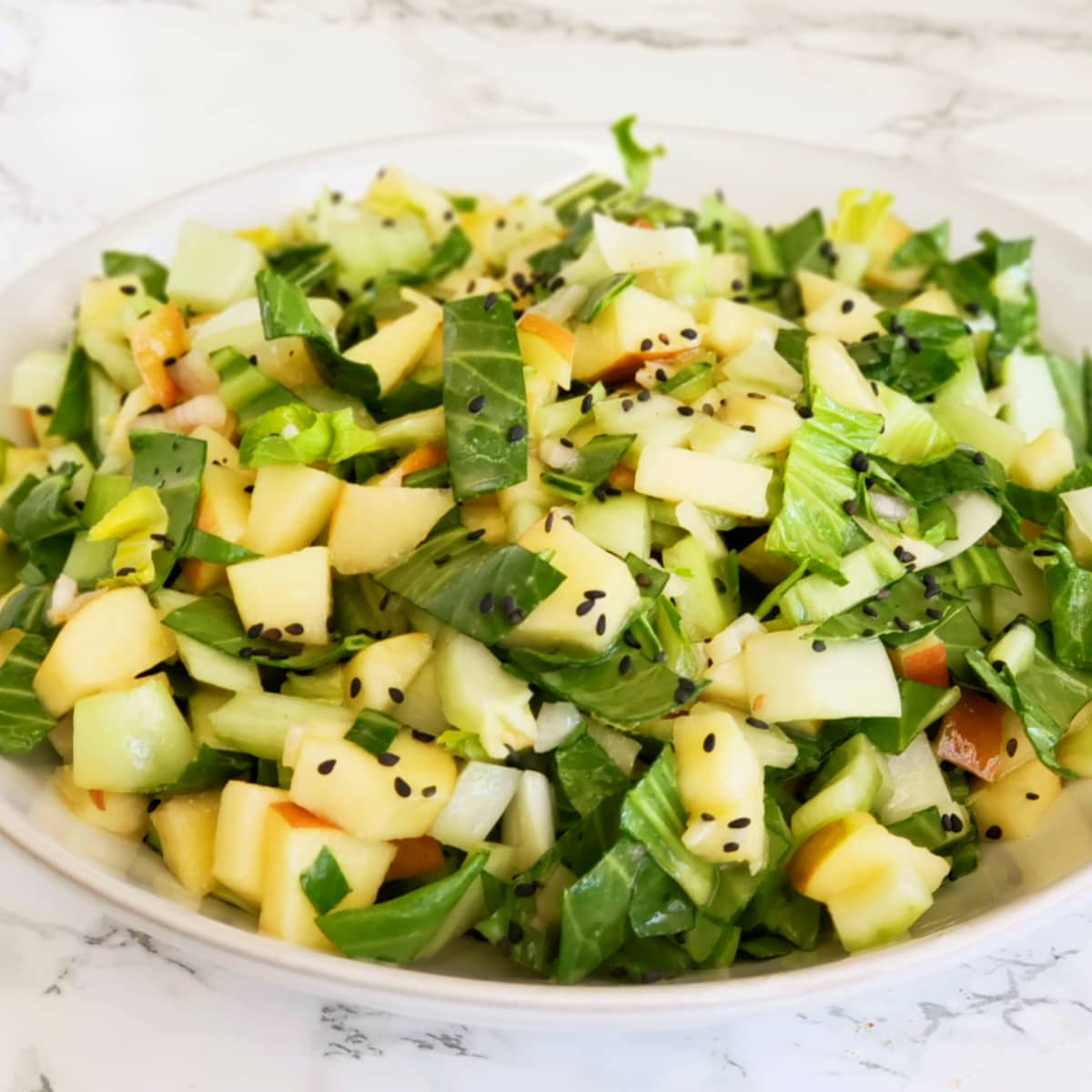 Lemony Baby Bok Choy, Apple and Miso Salad in a white bowl on a white marble counter top