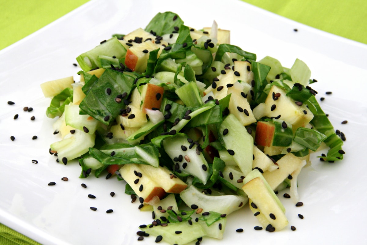 Baby bok choy and apple salad with lots of black sesame seeds sprinkled on top on a square white plate on a bright green placemat