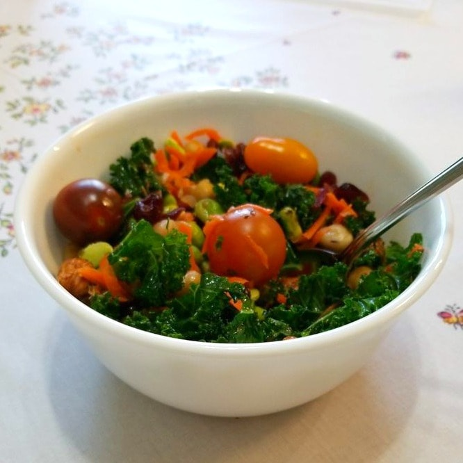 Kale salad with tomatoes on top in a white bowl photo by Katherine Wang