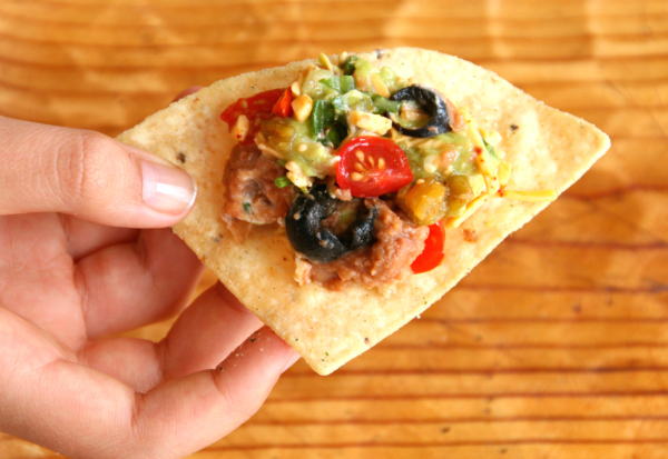 Walking Tostada or Mexican Seven-Layer Dip on a triangle tortilla chip on ShockinglyDelicious.com