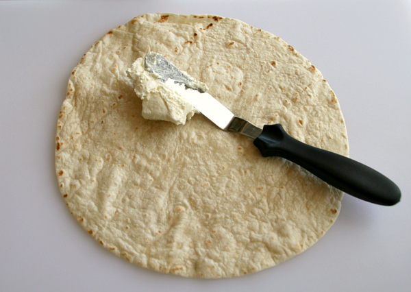 Spreading cream cheese on a tortilla for Poor Man's Burritos or Hatch Chile Roll-Up