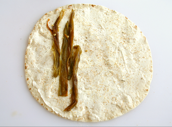 Lay Hatch chiles on cream cheese on tortilla for Poor Man's Burritos or Hatch Chile Roll-Up