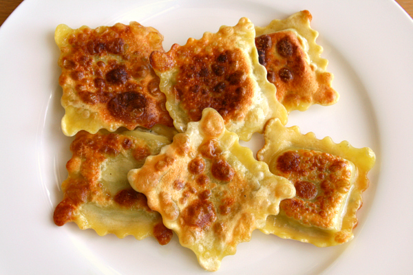 6 Crispy Ravioli browned from the skillet on a white plate