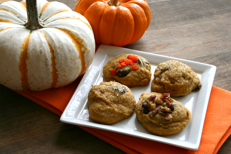 4 Pumpkin Chocolate Chip Cookies on a white plate with 2 small pumpkins to the side