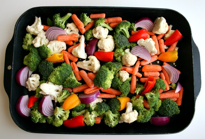 Mixed vegetables in a black baking dish on a white counter on Shockingly Delicious