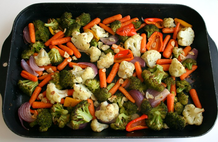 Roasted vegetables in a black baking pan on a white counter on Shockingly Delicious