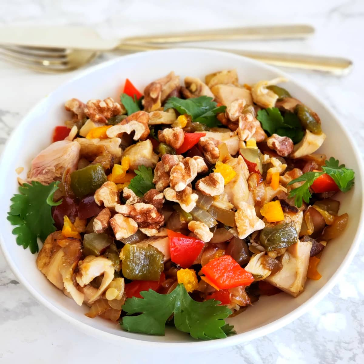 Chicken salad with salsa and walnuts on top in a white bowl on ShockinglyDelicious.com