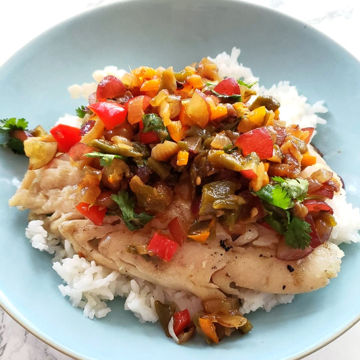 Hatch Chile Grape Salsa atop fish and rice in a light blue bowl