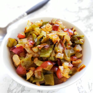 Chopped Hatch Chile, Grape and Grilled Onion Salsa in a white bowl on a white marble counter top with a serving spoon in the back on ShockinglyDelicious.com