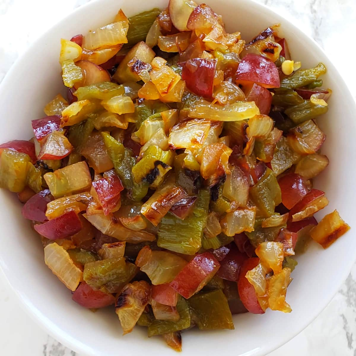 Chopped Hatch Chile, Grape and Grilled Onion Salsa piled in a white bowl on ShockinglyDelicious.com