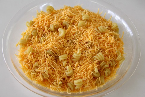 Shredded cheese and dry pasta is in the pie dish | www.ShockinglyDelicious.com