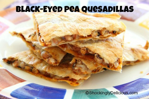 Black-Eyed Pea Quesadillas cut in wedges on a colorful plate with the recipe title superimposed