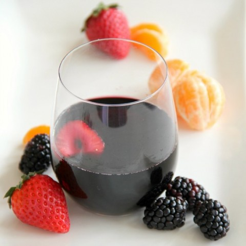 Fruity Burgundy Sangria in a glass with berries alongside | www.ShockinglyDelicious.com