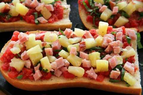 Assembling ingredients like ham, pineapple and tomatoes on top of French Bread Hawaiian Pizza