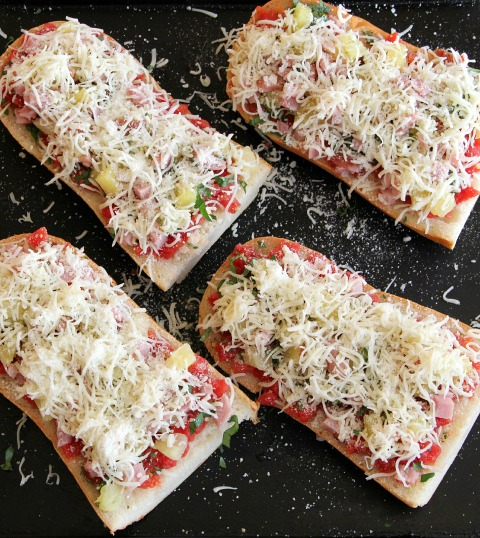 4 French bread pizzas ready for the oven with grated Parmesan on top