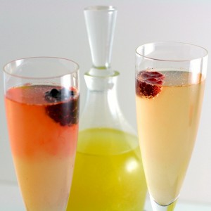 2 champagne flutes filled with berries floating on top