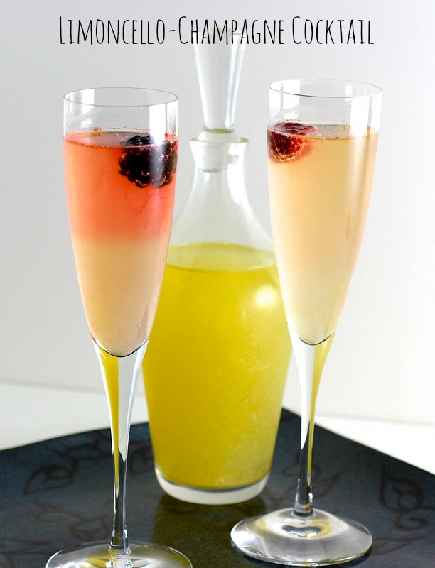 2 champagne flutes with Limoncello-Champagne Cocktail on a black tray