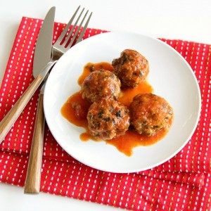 4 turkey meatballs on a white plate on a red napkin