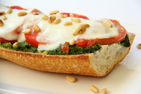 Pesto Caprese French Bread Pizza: A smear of basil pesto, a layering of perfectly fresh, ripe tomatoes, slices of soft fresh mozzarella, a quick pass through the oven, and you have easy pizza perfection. Don't forget to sprinkle the top with toasted pine nuts! #shockinglydelicious #pizzarecipe  #weeknightdinner  #pestopizza #frenchbreadpizza #capresepizza
