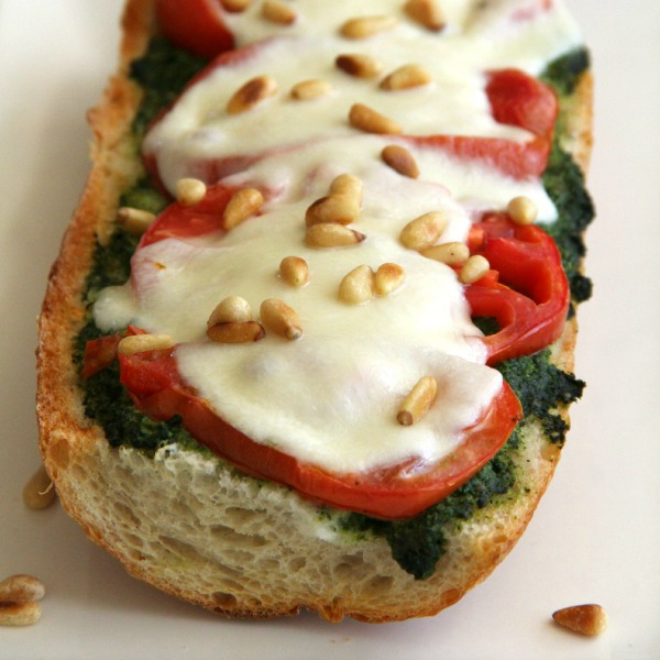 Pesto Caprese French Bread Pizza with pesto, tomato slices, mozzarella and pine nuts on top