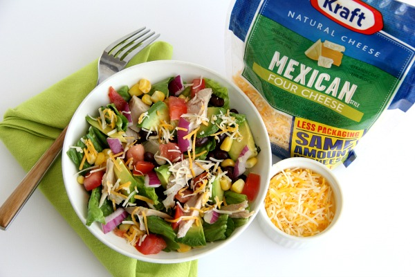 Salad in white bowl next to bag of Mexican cheese | Shockingly Delicious.com