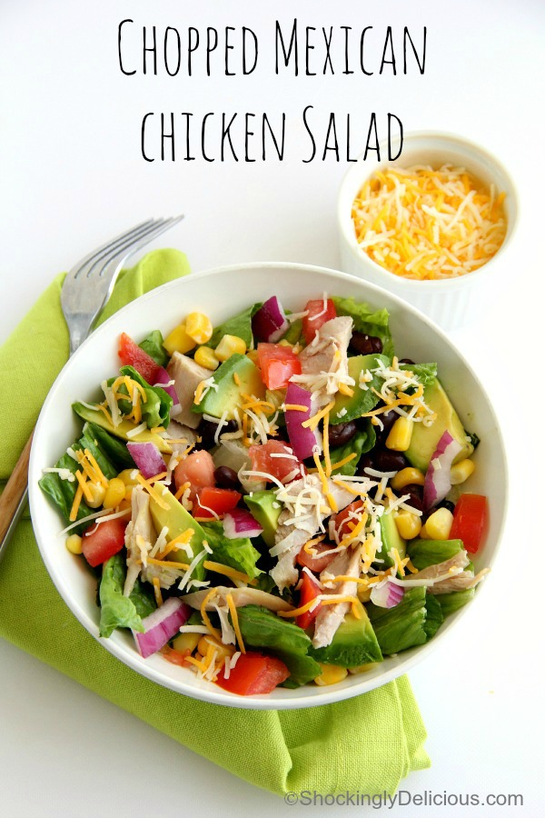 Chopped Mexican Chicken Salad on a green napkin with bowl of cheese on the side | Shockingly Delicious.com