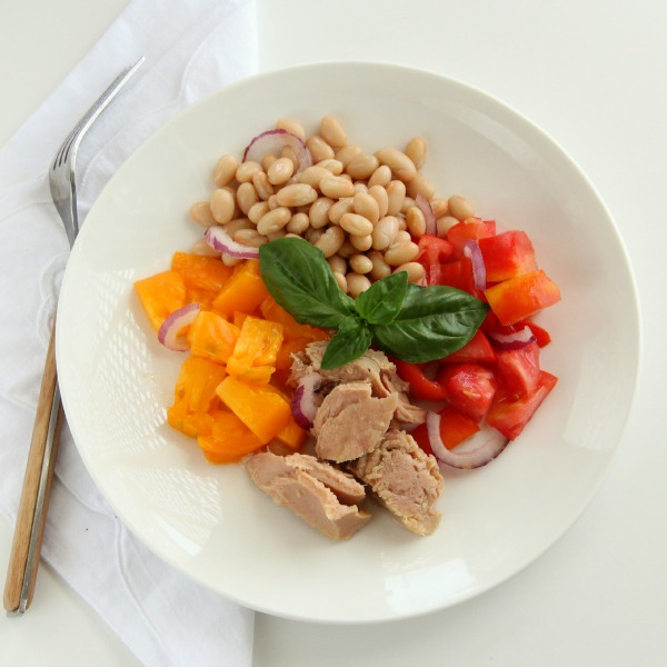 Tuna, Tomato, Bean and Basil Salad in a white bowl with a white napkin beside it