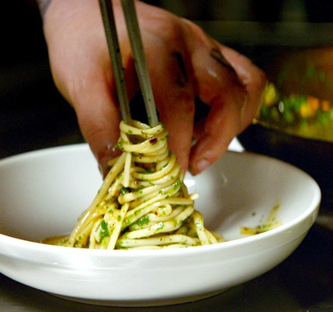 Pasta-Aglio-e-Olio-from-the-movie-chef being twisted around a metal skewer by a hand, in a white bowl