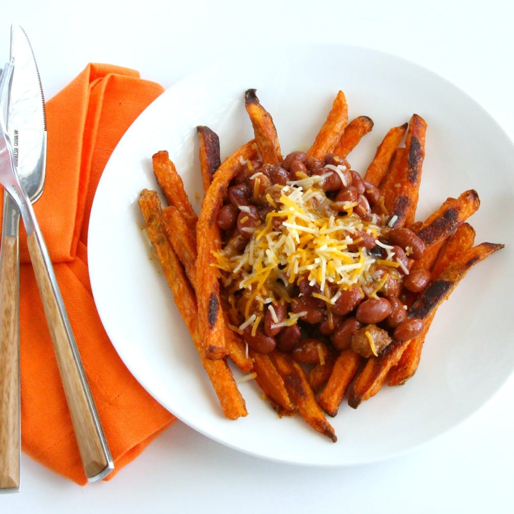 Sweet Potato Fries on a white plate with with Chili and Cheese on top on ShockinglyDelicious.com