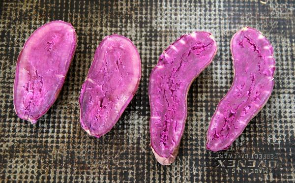 baked Purple Sweet Potato halves on a dark gray baking sheet
