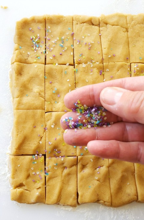Sprinkle Brown Sugar Shortbread with sugar crystals on ShockinglyDelicious.com