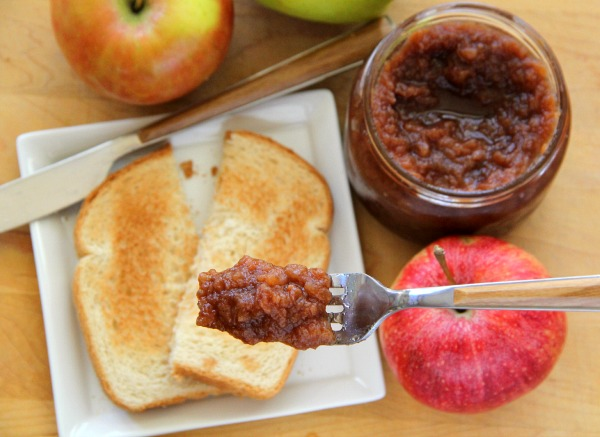 Slow Cooker Apple Butter on a fork in foreground, with toast, apples and jar of apple butter in background out of focus Recipe | ShockinglyDelicious.com