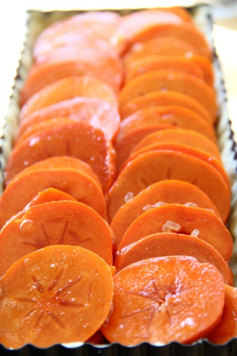 Sliced persimmons in tart shell for Persimmons Tart on ShockinglyDelicious.com