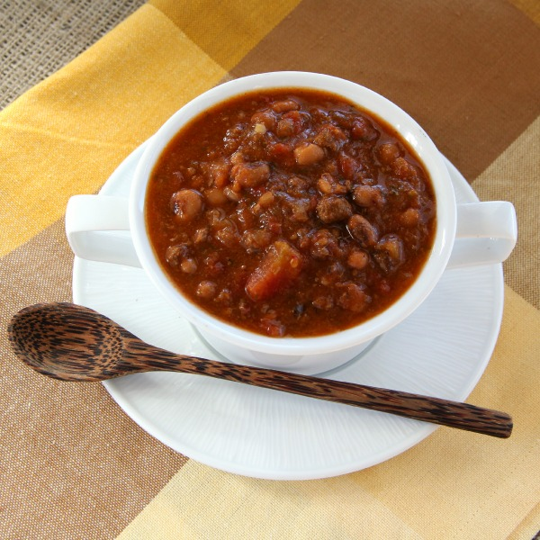 Slow Cooker Black-Eyed Pea Taco Soup in a white bowl on a white plate against a brown and yellow napkin