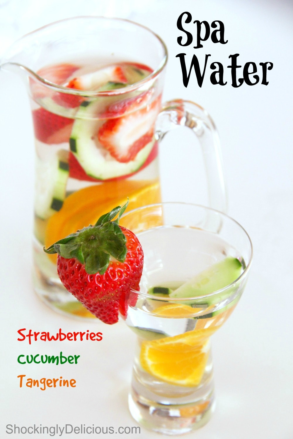 Glass of water with cut fruit in it in front of a pitcher of water with fruit in it