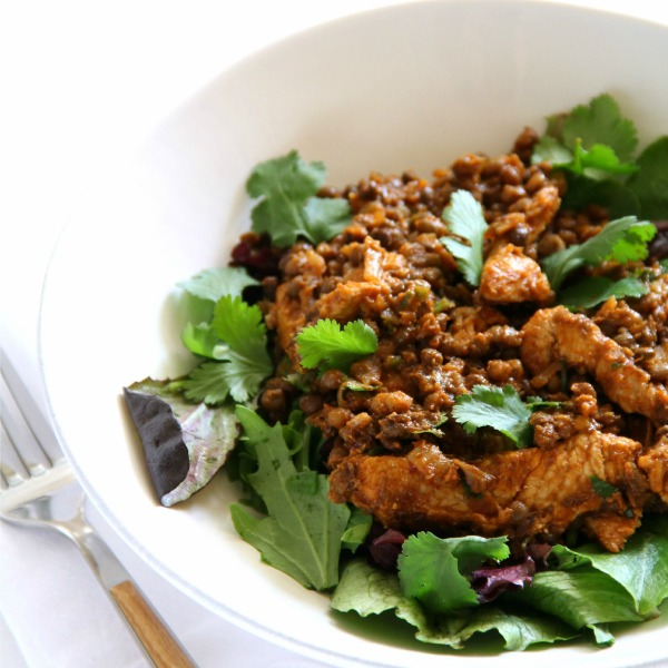 Turkey Lentil Taco Salad over salad greens in a white bowl with a fork alongside