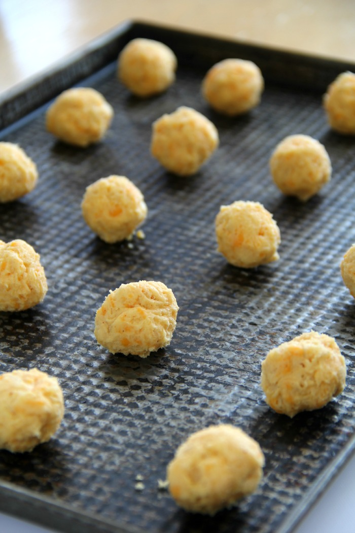 Dark cookie sheet full of cheese balls ready for the oven